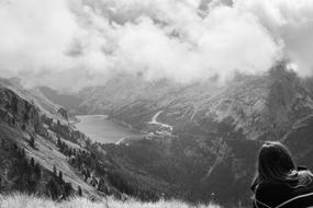 monochrome photo of a girl sitting on a mountain top