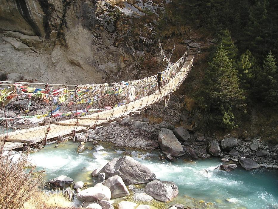 photo of a suspension bridge in the mountains in Nepal