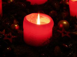 burning red wax candle in advent wreath