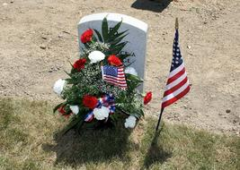 Flowers and american flags at gravestone