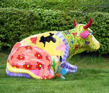 multi-colored sculpture of a cow on a lawn in a park