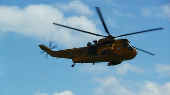 rescue yellow helicopter high in the blue sky