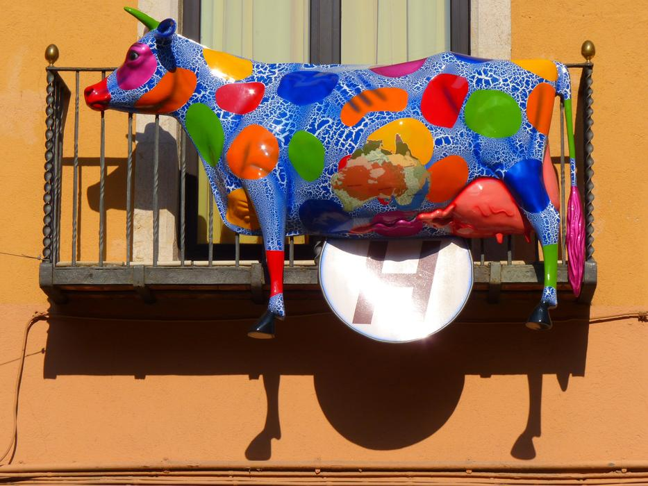 multi-colored sculpture of a cow on the balcony