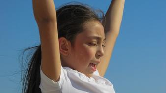 photo of a girl with hands up against a blue sky