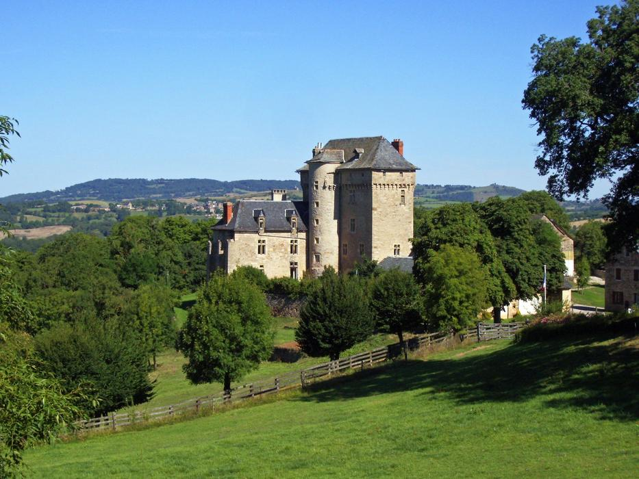 medieval castle on a green hillside in Aveiron, France