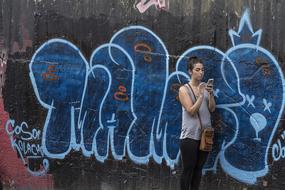 girl with a smartphone on the background of a wall with graffiti