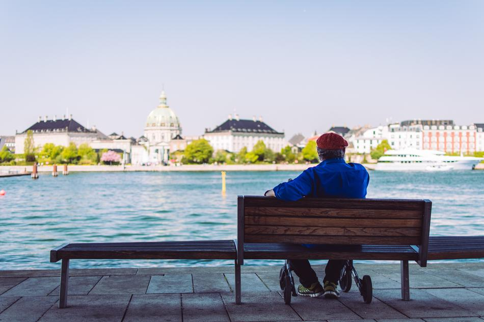 man sits on Bench on waterfront in view of old city