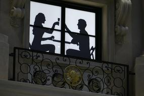 silhouette of a couple at a table on a balcony in Macau, China