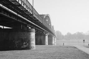 black and white photo of a railway bridge over a river