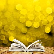 Open book on the wooden surface at yellow background with bokeh lights