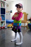 funny child Girl in dark glasses and cap indoor