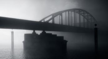 Black and white bridge above the water in fog