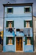 clothes are dried on a rope on the facade of a building on the island of Burano in Italy