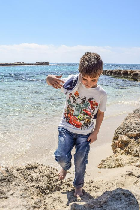 Child Boy playing in sand on beach