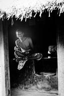 black and white photo of a poor man sitting on a stump in a hut
