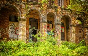 graffiti and inscriptions on an abandoned brick building