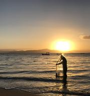 Fisherman with net standing in water on beach at sunset