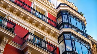 red building facade and black lattice balconies in Madrid, Spain