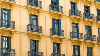 yellow building facade and black grilles on balconies in Madrid, Spain