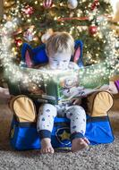 Winter tale, Child boy reading book at christmas tree