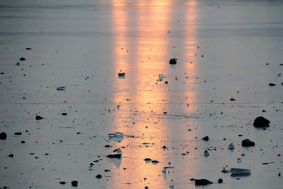 the reflection of the evening sun on the surface of a frozen lake