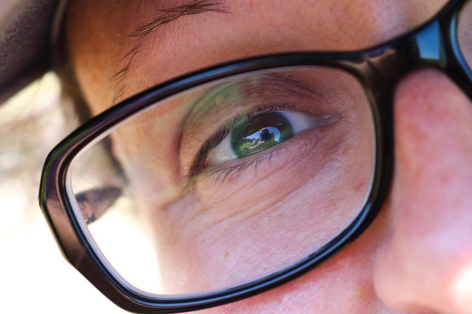 Close-up of the person's green eye in glasses