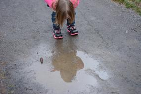 girl looks at reflection in a puddle