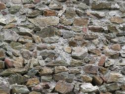 sharp stones sticking out of the stone wall