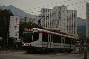 photo of a white tram on a street in Hong Kong