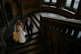 newlyweds descend the castle stairs