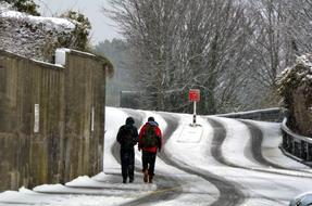 two men Walking uphill on road at winter