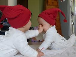 two newborn twins in christmas caps