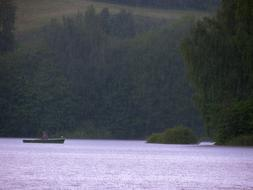 distant view of the boat on the lake in the forest in the rain