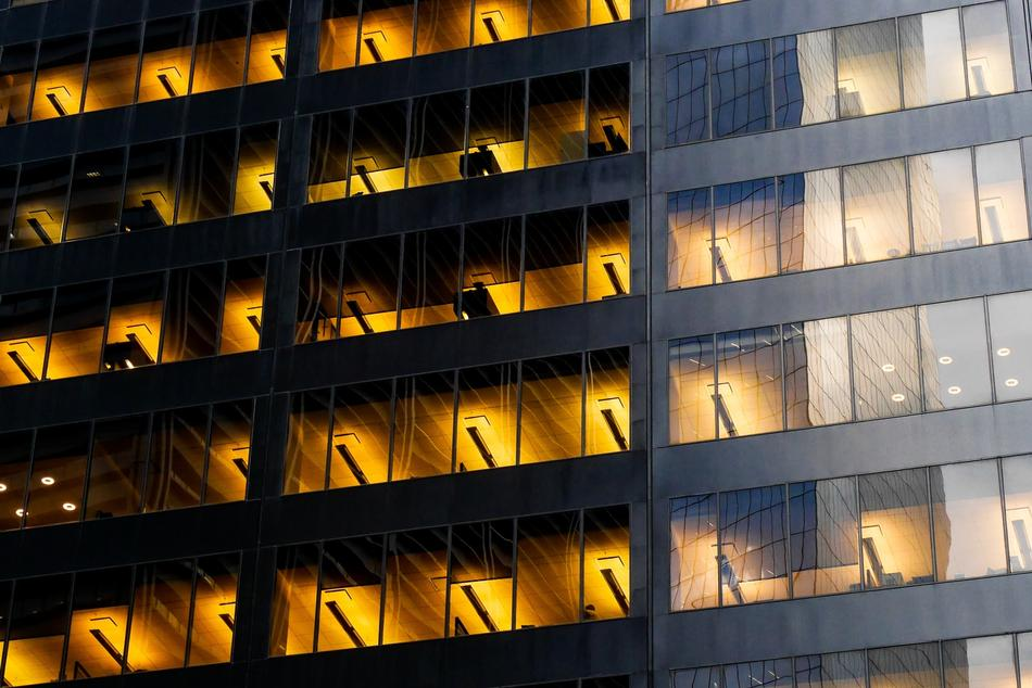yellow light in the windows of a glass skyscraper