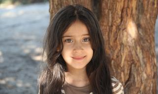 photo of a girl with long hair on a background of a brown tree trunk
