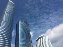 photo of three glass skyscrapers against a cloudy sky