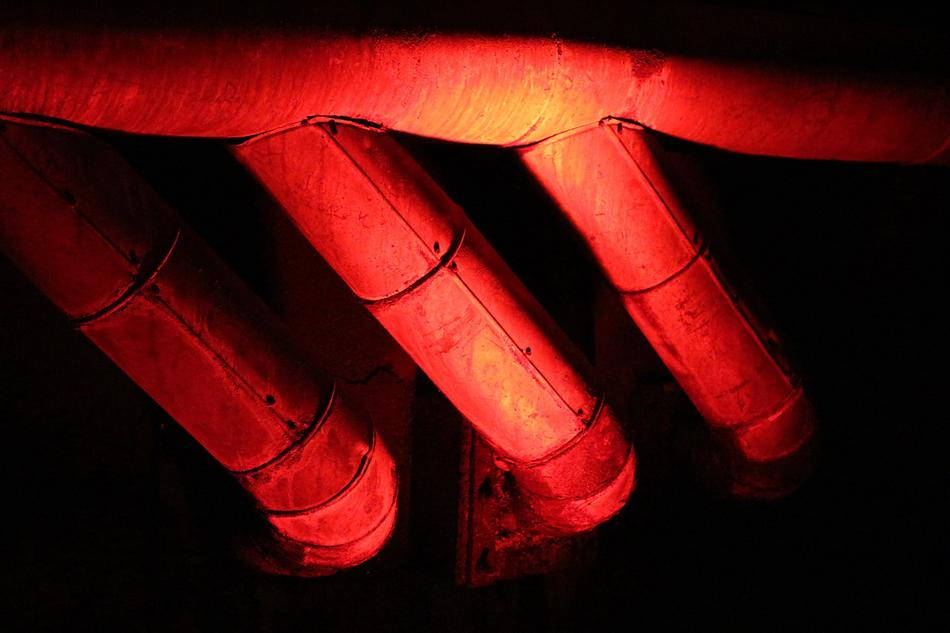 Metal pipes in red and orange colors, among the darkness
