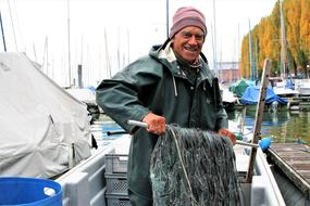 senior fisherman with fishing net on boat