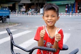 happy asian child boy thumbs up in city
