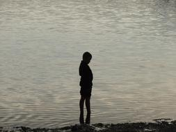 silhouette of a boy standing by the lake