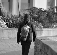 Man with backpack walking away