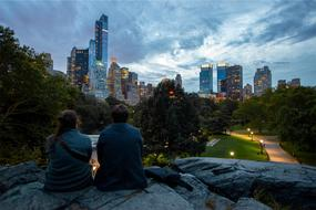Couple sitting on rock in front of city at dusk