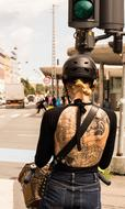 Girl with tattoo on back riding Bike in city