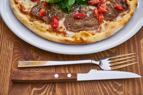 photo of pizza, fork and knife on the table