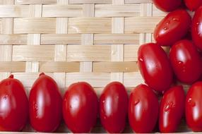 wet cherry tomatoes on wicker background